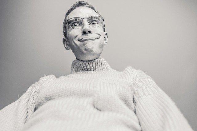 Muž v okuliaroch a pletenom svetri robí grimasy