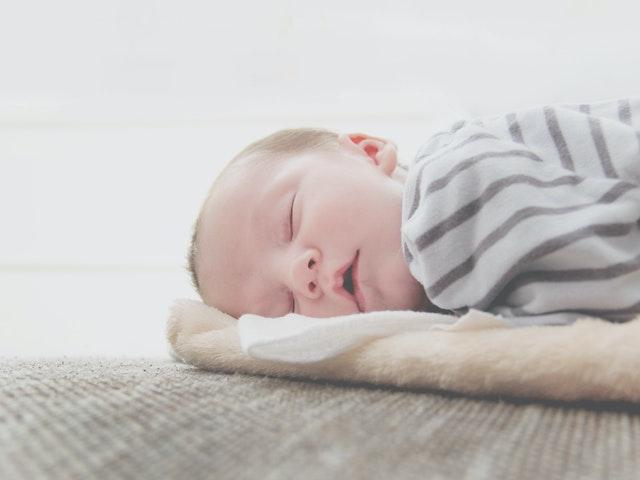 Bábätko v pásikovom oblečení spí s otvorenými ústami